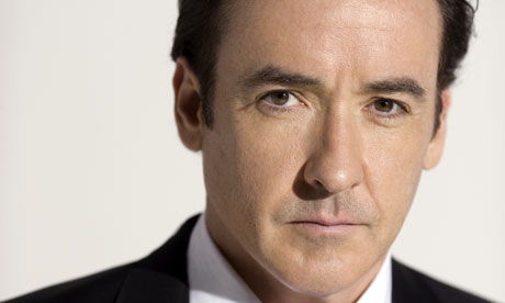 John Cusack with a serious expression wearing a suit and tie